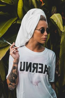 Free Woman Wearing White Crew-neck Shirt And Black Framed Sunglasses With White Bath Towel On Her Head Holding Cigarette Stick Royalty Free Stock Photography - 116927707