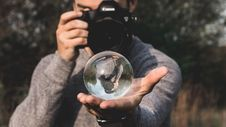 Free Man Wearing Space-dyed Sweater Holding Water Globe While Holding Black Canon Camera Royalty Free Stock Image - 116927756