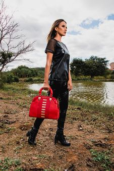 Free Woman Wearing Black Suit Holding Red Leather Duffel Bag During Day Stock Images - 116927824