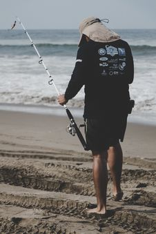 Free Man In Black Long-sleeved Top Holding White Fishing Rod Near Beach Royalty Free Stock Photography - 116984387