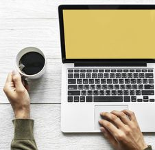 Free Person S Hand On Laptop And Holding Coffee Stock Photography - 116984432