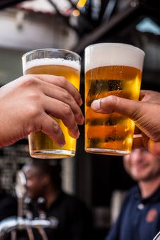 Free Two Persons Holding Drinking Glasses Filled With Beer Royalty Free Stock Image - 116984486