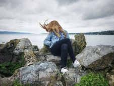 Free Woman With Blue Denim Collared Button-up Jacket And Black Jeans Sitting On Gray Rock Watching Lakeview Stock Photography - 116984572