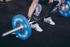 Free Man With Lift Stance Holds Blue Rogue Adjustable Barbell Royalty Free Stock Photos - 116984628