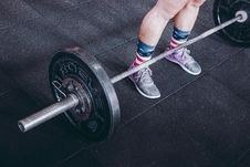 Free Person Standing Near Black Barbell Stock Image - 116984631