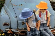 Free Two Boy In Grey Shirts And Blue Overall Pants Sitting On Blue Car Bumper Royalty Free Stock Photography - 117112417