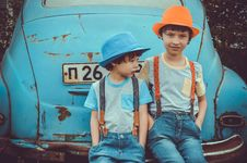 Free Two Boys Sitting On Blue Volkswagen Beetle Coupe S Rear Bumper Royalty Free Stock Photo - 117112435