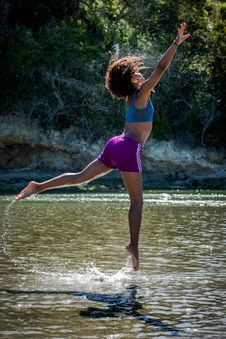 Free Woman In Blue Sports Bra And Purple Shorts Leaping Above Body Of Water Royalty Free Stock Photography - 117112437