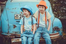 Free Two Boys Sitting On Classic Blue Car S Rear Bumper Stock Photo - 117112440