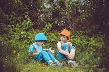 Free Girl And Boy Sitting On Grass Field Surrounded By Trees Stock Image - 117112441