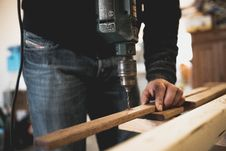 Free Man Holding Wooden Stick While Drilling Hole Stock Images - 117112474