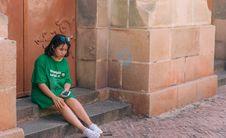 Free Woman Wearing Green Shirt Sitting Near Brown Gate Holding Smartphone Royalty Free Stock Photo - 117112745