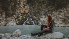 Free Woman With Brown Hair In Black Jacket Sitting On Rock Near Body Of Water Stock Photography - 117112822