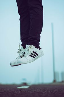 Free Person Wearing Pair Of White Adidas Superstar Shoes Stock Image - 117112911