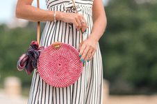 Free Woman Wearing White And Black Striped Dress Holding Her Red Sling Bag Royalty Free Stock Photography - 117112917