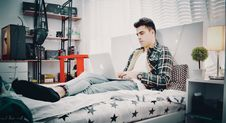 Free Man In Green, Blue, And Black Plaid Sports Shirt Sitting On Bed Using Silver Macbook Royalty Free Stock Photography - 117280637
