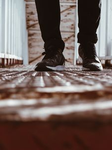 Free Person In Black-and-white Shoes Standing On Brown Metal Floor Royalty Free Stock Photos - 117280638