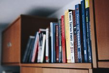 Free Assorted Books On Brown Wooden Shelf Royalty Free Stock Photo - 117280665