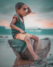 Free Boy Sitting On Canoe Near Body Of Water Taken Under White Clouds Stock Photos - 117352463