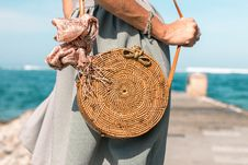 Free Woman Wearing Grey Skirt And Round Brown Rattan Crossbody Bag On Wooden Dock Near Body Of Water Royalty Free Stock Photo - 117352535