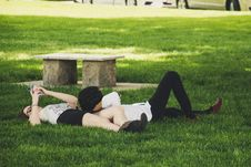 Free Man And Woman Laying On Green Grass Near Concrete Bench Royalty Free Stock Images - 117352599