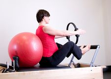 Free Woman In Red Top Leaning On Red Stability Ball Stock Photography - 117352612