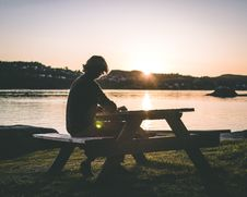 Free Silhouette Of Person In Black Top Sitting On Picnic Bench Near Body Of Water During Sunset Stock Photography - 117352852