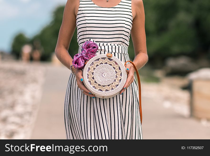 af0b9d42339 Woman Wearing White And Black Striped Sleeveless Dress Holding Round  Crochet Bag