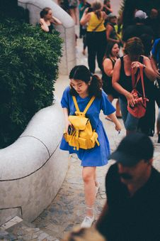 Free Woman In Blue Dress With Yellow Knapsack Walking Near People Royalty Free Stock Image - 117420866