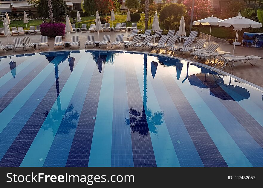 Beautiful reflection in clear water of blue swimming pool with chaise-longues in luxury resort hotel