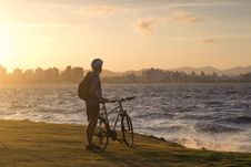 Free Man With Bicycle Standing On Cliff Front Of Water Waves Golden Hour Photography Royalty Free Stock Image - 117486156