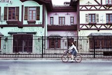 Free Woman Riding On Bicycle Near Concrete Houses Stock Images - 117486314