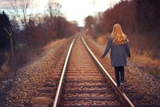 Free Woman In Blue Jacket And Blue Jeans Walking On Train Track Photography Royalty Free Stock Image - 117536866