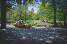 Free Yellow Ford Crown Victoria On Gray Concrete Pathway Stock Photo - 117536880