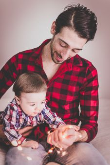 Free Man Wearing Red And Black Gingham Sports Shirt With Baby Beside Him Stock Images - 117536934