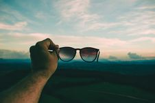 Free Person Holding Black Framed Sunglasses Under Blue Sky And White Clouds Royalty Free Stock Photo - 117608655