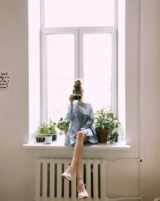 Free Woman In Grey Long-sleeved Dress Sitting On Window Stock Images - 117689004