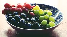 Free Red, Black, And Green Grapes In Round Blue And White Floral Ceramic Bowl Royalty Free Stock Image - 117689016