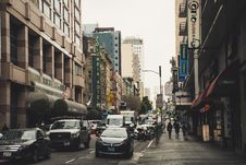 Free Busy Street With Vehicles And People Walking Beside Buildings Royalty Free Stock Images - 117689209