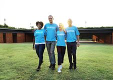 Free Four People Wearing Blue Crew-neck Shirts Standing On Lawn Stock Photography - 117689322