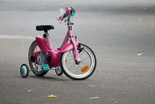 Free Pink Bike With Training Wheels On Gray Pave Road Royalty Free Stock Images - 117768049