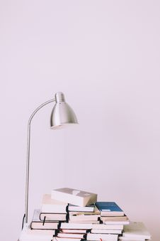 Free Silver Desk Lamp Near Pile Of Books Royalty Free Stock Photos - 117852778