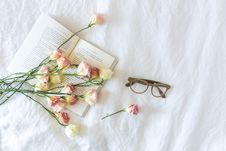 Free White And Pink Flowerson A Book Beside Eyeglasses Royalty Free Stock Photo - 117852995