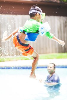 Free Boy In Green Crew-neck Shirt And Orange Shorts Jump Over Swimming Pool Stock Photos - 117917263