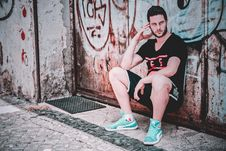 Free Man In Black T-shirt And Shorts Leaning On Wall Stock Image - 117988901