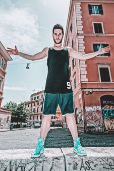 Free Man In Black Tank Top And Green Shorts Posing Near Building Royalty Free Stock Image - 117988926