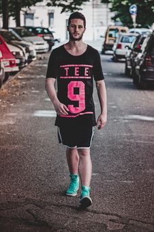 Free Man Wearing Black Crew-neck T-shirt, Black Shorts, And Pair Of Teal High-top Sneakers Walking Between Vehicles Stock Photo - 117988930