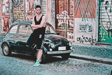 Free Man In Black Tank Top Standing Beside Black 3-door Hatchback Royalty Free Stock Image - 117988966