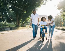 Free Man Standing Beside His Wife Teaching Their Child How To Ride Bicycle Royalty Free Stock Image - 117989026