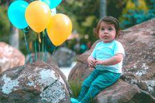 Free Toddler Wearing White Shirt Sitting On Rock Beside Yellow And Blue Balloons Royalty Free Stock Photos - 117989228